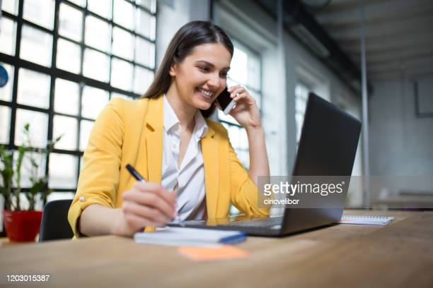 young businesswoman multi-tasking at her office - economist stock pictures, royalty-free photos & images