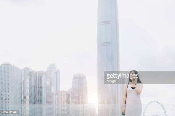 Young businesswoman on a business call outdoors against urban city skyline in morning