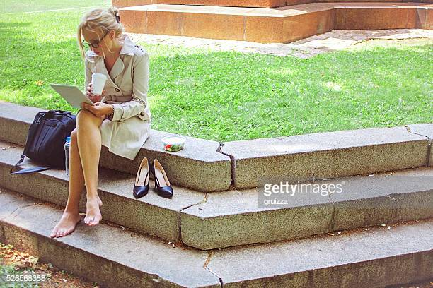 young businesswoman on a lunch break in park - lunch break stock photos and pictures