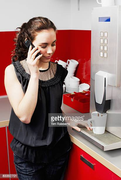 Young businesswoman on mobile at coffee machine