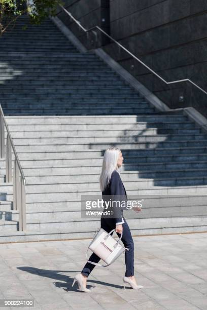 young businesswoman on the go in the city - long purse stock photos and pictures