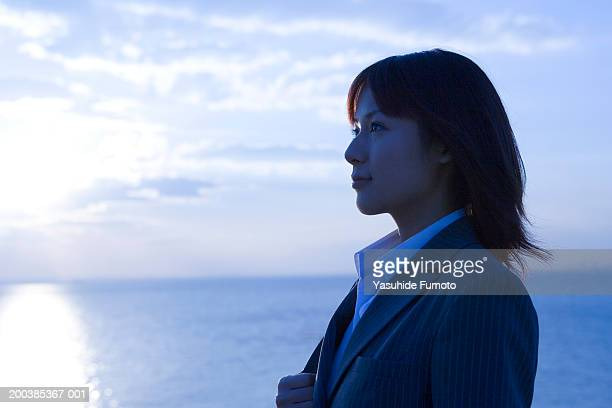Young businesswoman outdoors, near water, side view