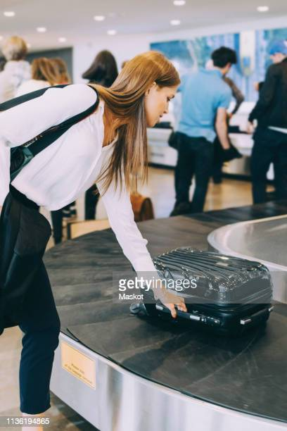 young businesswoman picking luggage from conveyor belt at airport - baggage claim stock pictures, royalty-free photos & images
