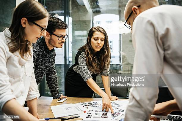 young businesswoman pointing at project papers - design foto e immagini stock