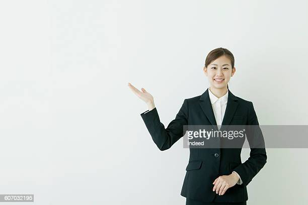 Young businesswoman pointing blank wall