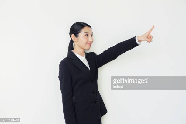 Young businesswoman pointing finger up