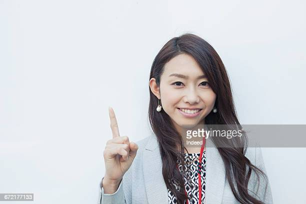 Young businesswoman pointing up with index finger