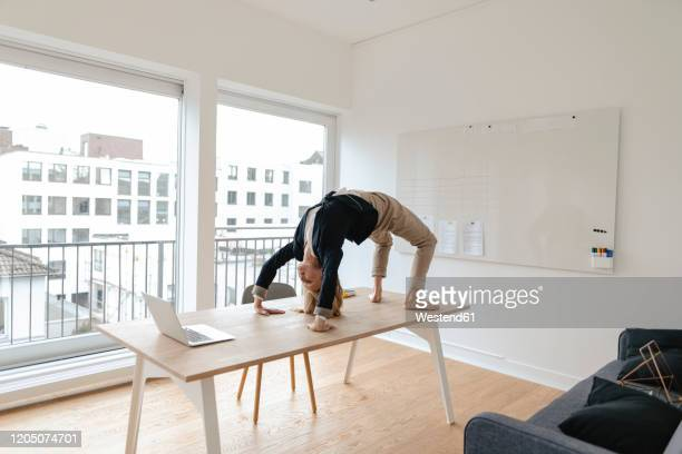 young businesswoman practicing yoga on desk in office - bizarre stock pictures, royalty-free photos & images