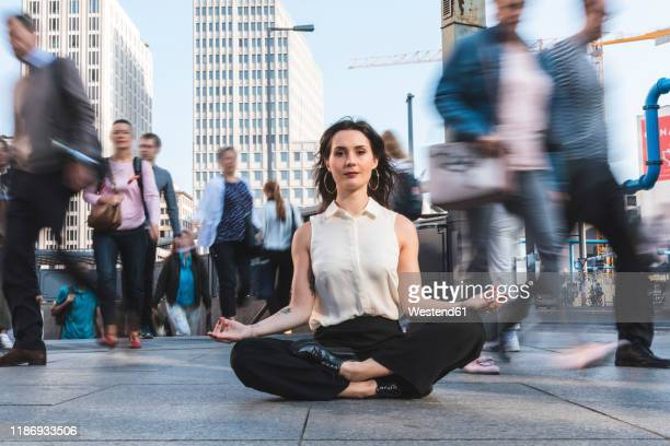 young businesswoman practising yoga in the city at rush hour, berlin, germany - human settlement stock pictures, royalty-free photos & images
