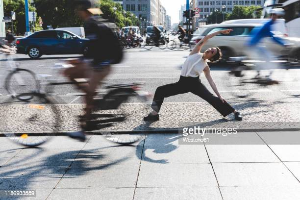 young businesswoman practising yoga in the city at rush hour, berlin, germany - körperbewusstsein stock-fotos und bilder