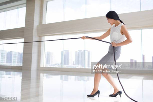 Young businesswoman pulling rope