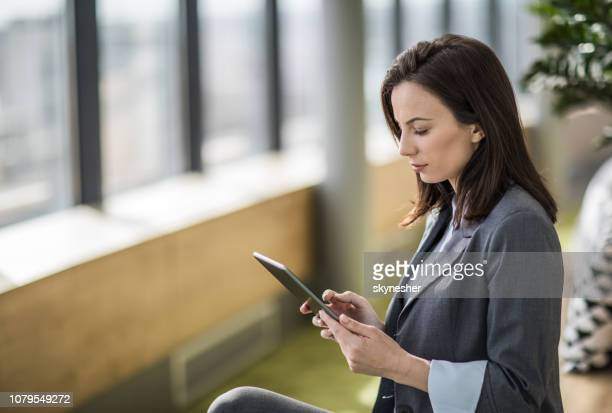 young businesswoman reading an e-mail on touchpad in a hallway. - economist stock pictures, royalty-free photos & images