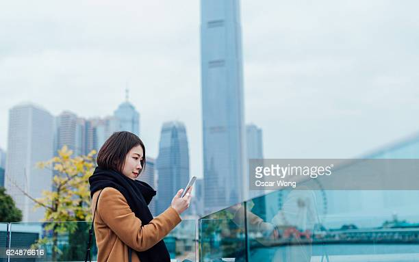 Young businesswoman reading email on smartphone against city background