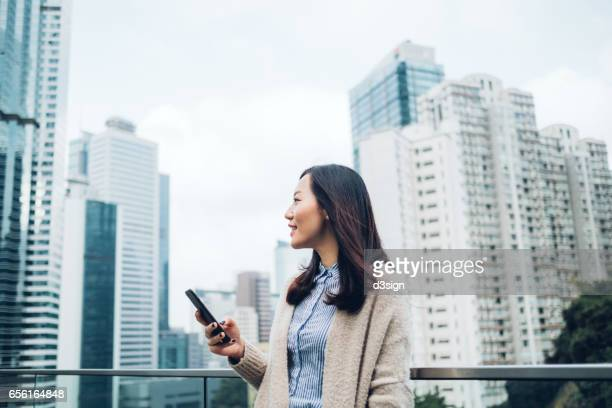 Young businesswoman reading emails on smartphone by the terrace of office building