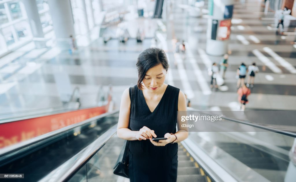 Young businesswoman reading emails on smartphone while riding on escalator : Stock Photo