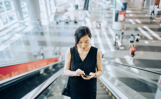 Young businesswoman reading emails on smartphone while riding on escalator - gettyimageskorea