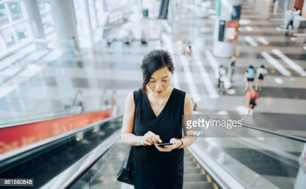 young businesswoman reading emails on smartphone while riding on escalator - china oost azië stockfoto's en -beelden