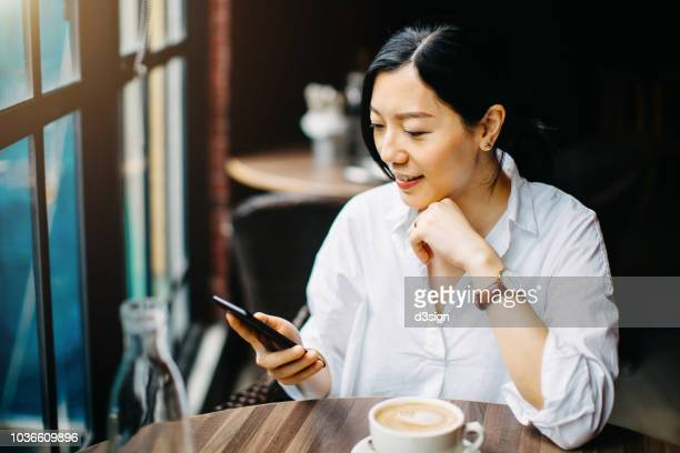 young businesswoman reading news on smartphone and drinking coffee in cafe in the morning - simple living stock pictures, royalty-free photos & images