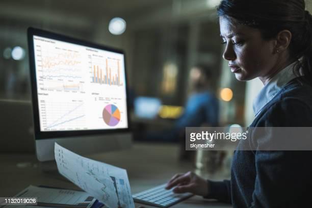 若いビジネスウーマンは、オフィスで pc で遅く作業しながらレポートを読んでいます。 - report document ストックフォトと画像