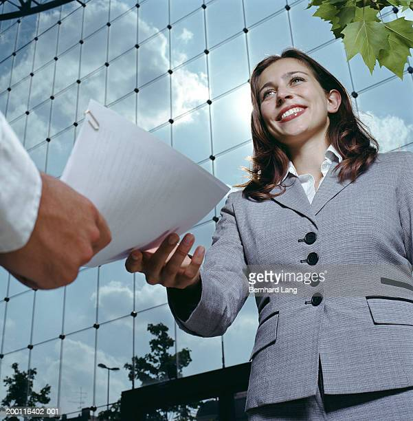 Young businesswoman receiving document outdoors, low angle view