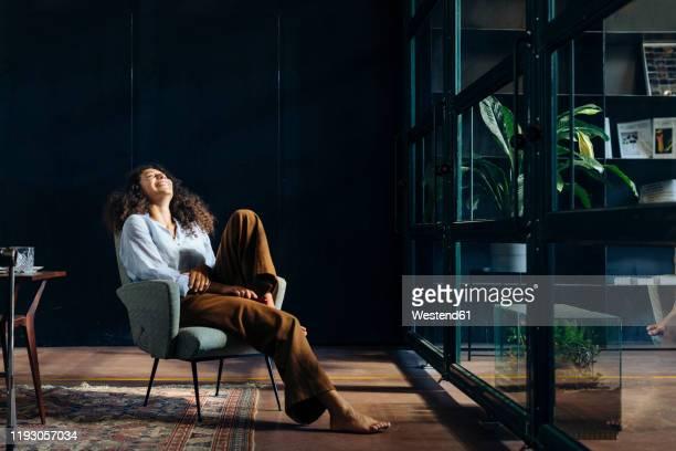 young businesswoman relaxing in loft office - être à l'aise photos et images de collection