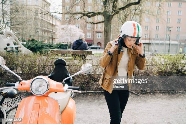 young businesswoman removing helmet while walking by motor scooter on roadside in city - sportschutzhelm stock-fotos und bilder