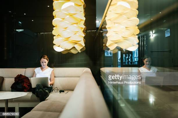 Young Businesswoman Sat In Hotel Bar Working On Laptop