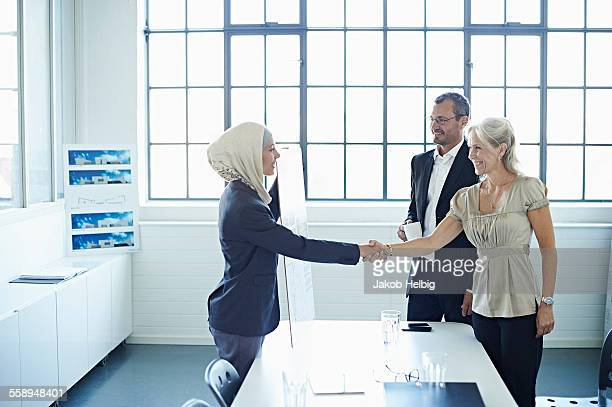 Young businesswoman shaking hands with businesswoman in office