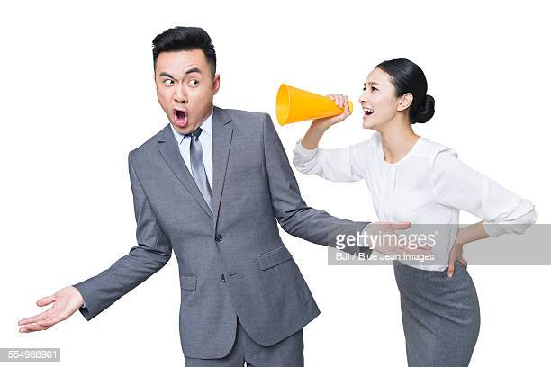 Young businesswoman shouting at businessman through megaphone
