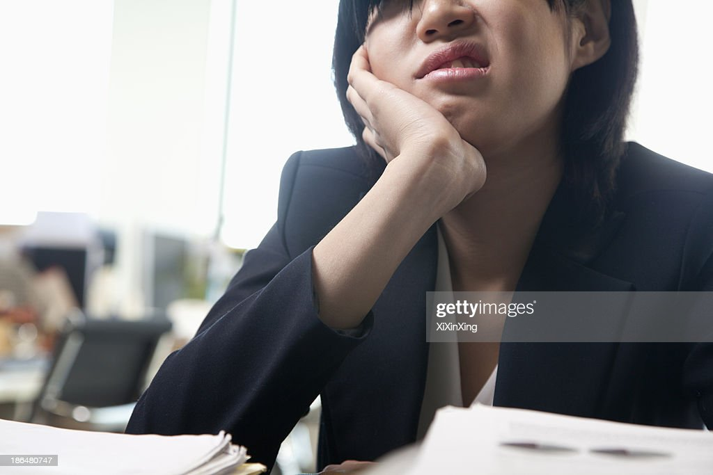 Young businesswoman sitting at desk bored : Stock Photo