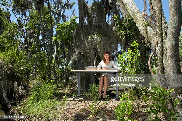 Young businesswoman sitting at desk in woods, portrait