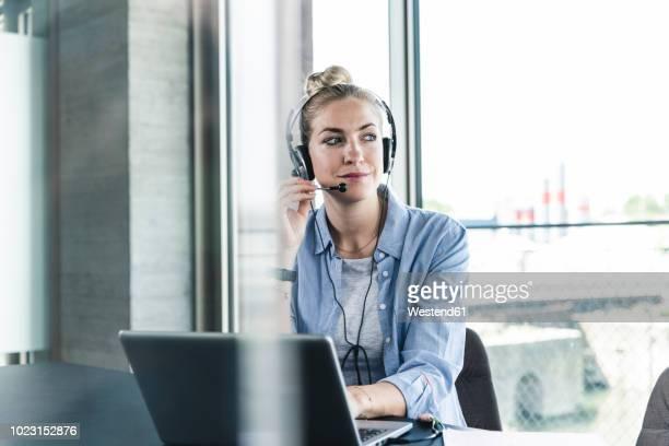 young businesswoman sitting at desk, making a call, using headset and laptop - dienstleistung stock-fotos und bilder
