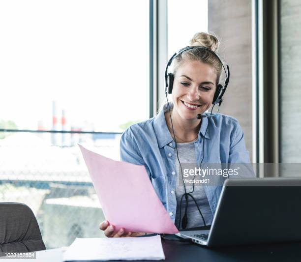 young businesswoman sitting at desk, making a call, using headset and laptop - arbeitszimmer stock-fotos und bilder