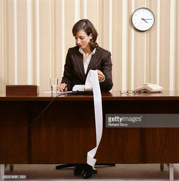 young businesswoman sitting at desk using calculator - length stock pictures, royalty-free photos & images