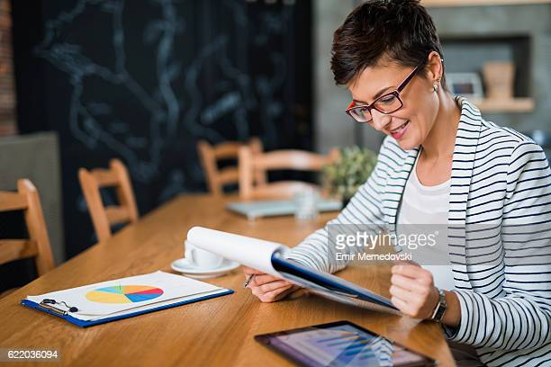 Young businesswoman sitting at the office reading business report.