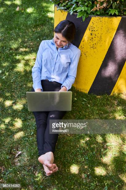 young businesswoman sitting barefoot on a meadow using laptop - looking down her blouse stock photos and pictures