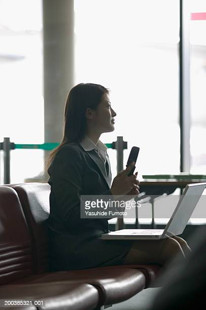 Young businesswoman sitting in airport with laptop, holding phone