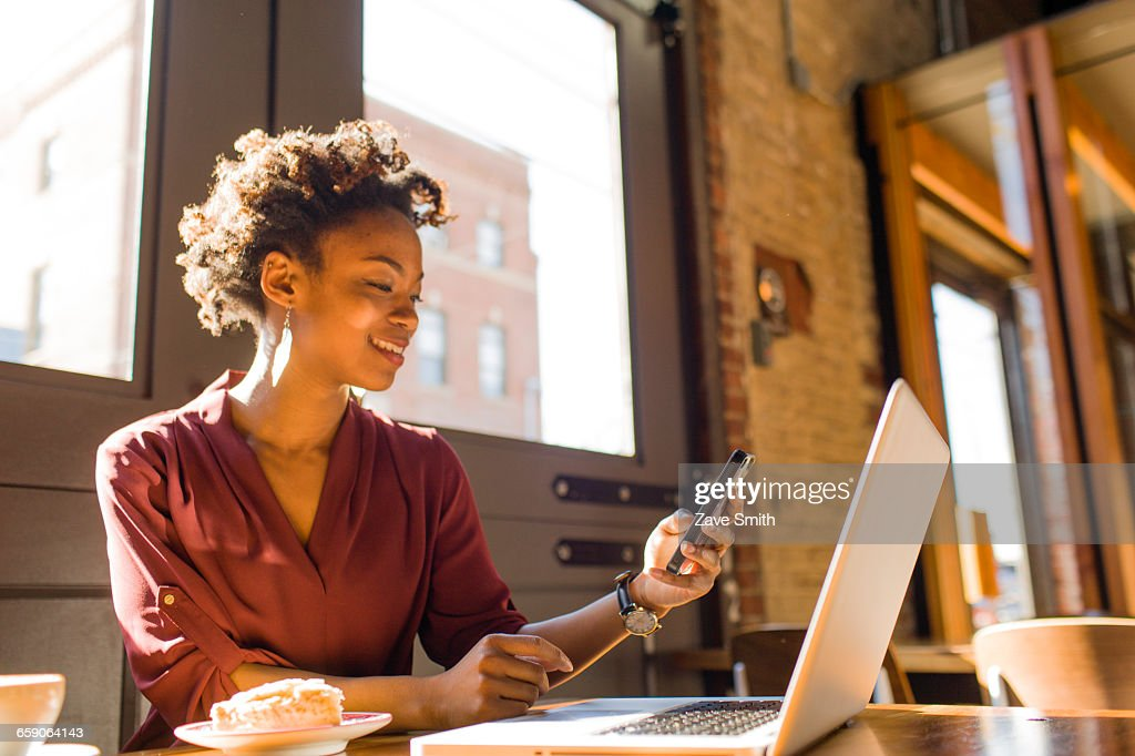 Young businesswoman sitting in cafe, using laptop and smartphone : Stock Photo