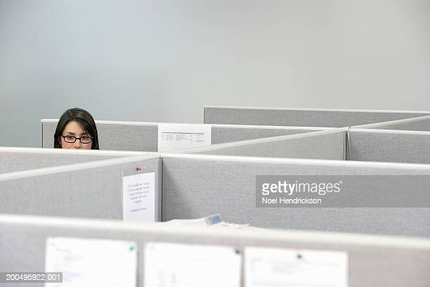 young businesswoman sitting in cubicle, high section - office cubicle stock pictures, royalty-free photos & images