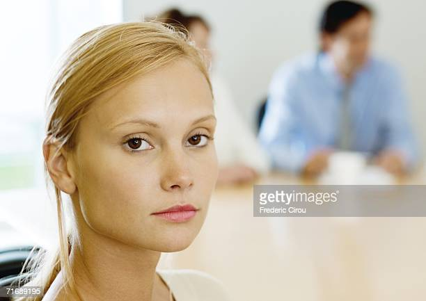 Young businesswoman sitting in meeting, looking at camera