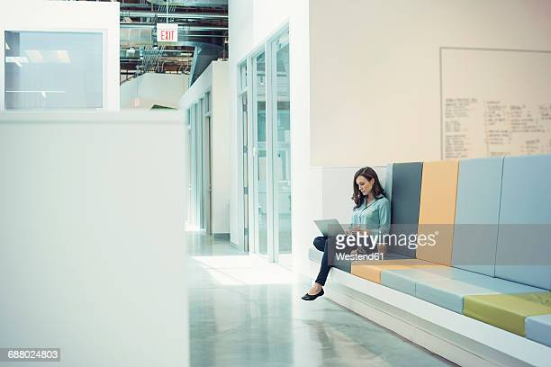 Young businesswoman sitting on bench, using laptop