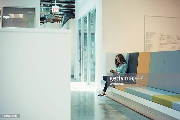 Young businesswoman sitting on bench, using smart phone