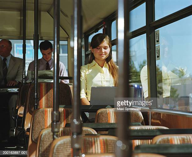 Young businesswoman sitting on bus, using laptop