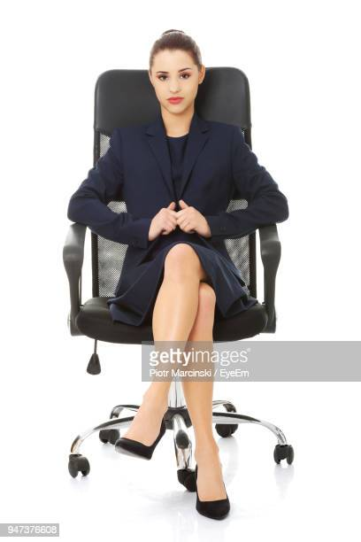 Young Businesswoman Sitting On Chair Against White Background