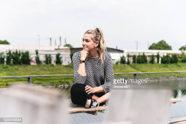 young businesswoman sitting outdoors, taking a break - 僅一名年輕女人 個照片及圖片檔