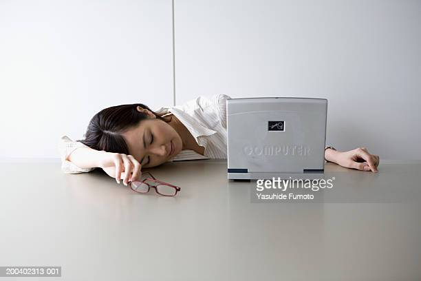 Young businesswoman sleeping on desk, near laptop