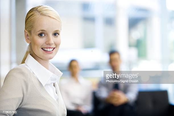 Young businesswoman smiling at camera, head and shoulders, portrait