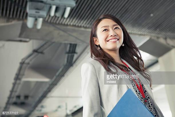 Young businesswoman smiling under highway