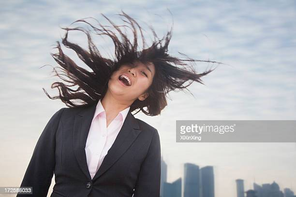 Young businesswoman smiling with hair blowing