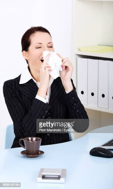 Young Businesswoman Sneezing While Working In Office